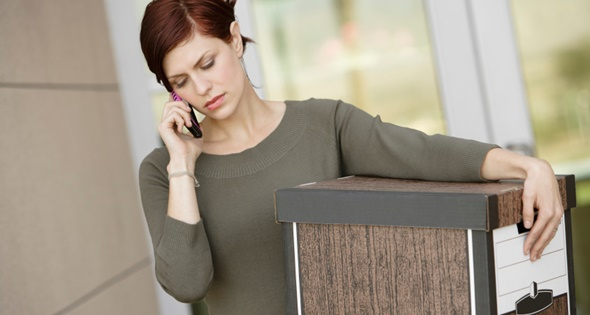 Upset young businesswoman using mobile phone while carrying moving box