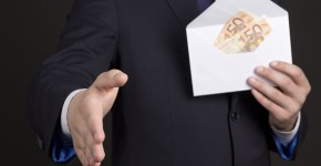 bribery concept - man in suit with money in white envelope ready to handshake